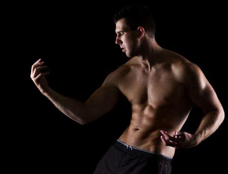 Strong muscular man gracefully posing on black photo