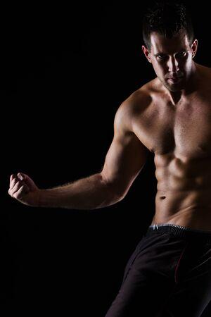 Strong muscular man posing on black photo