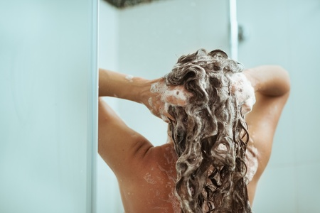 Woman washing away shampoo in shower. Rear view photo