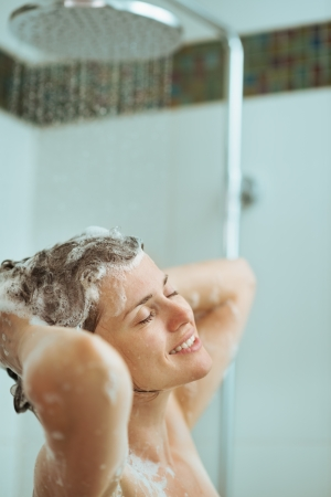 Happy woman washing hair with shampoo in shower Stock Photo - 14961653