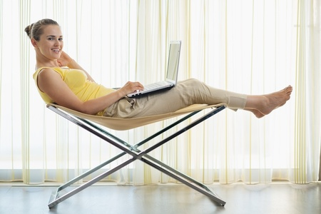 Happy young woman sitting on modern chair and working on laptop Stock Photo - 14961643