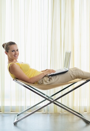 Smiling young woman sitting on modern chair and working on laptop Stock Photo - 14961641
