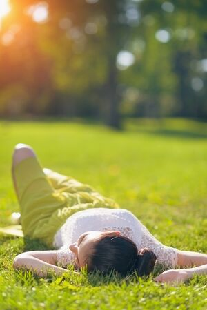 Young woman relaxing on meadow. Rear view Stock Photo - 15014891