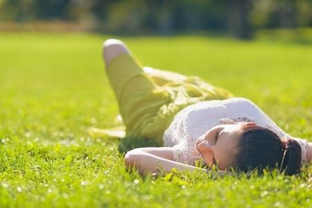 Young woman relaxing on grass. Rear view Stock Photo - 15014873