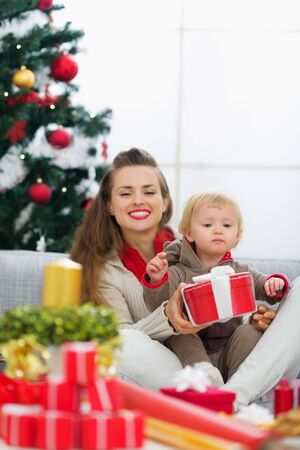 Happy young mother and baby looking on table with Christmas gifts Stock Photo - 15015051