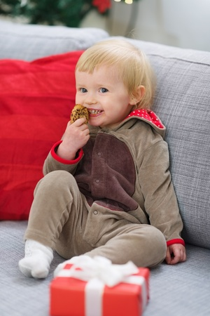 Happy baby in deer suit with Christmas present box eating cookie Stock Photo - 15015234