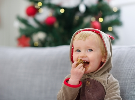 holiday cookies: Happy baby in Christmas suit eating cookie Stock Photo
