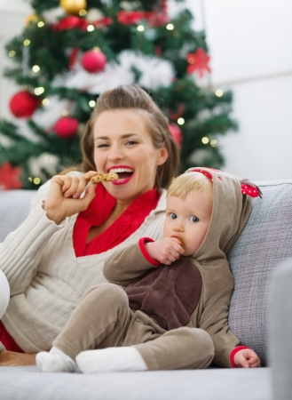 Happy young mother and baby eating cookies near Christmas tree Stock Photo - 15015230
