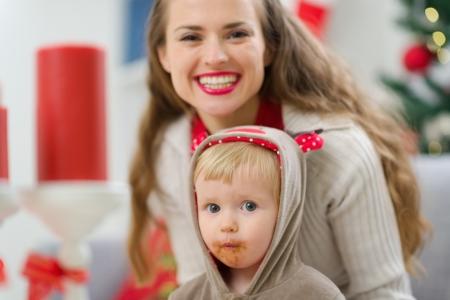 smeared baby: Retrato de la sonrisa joven madre y su beb� comer untado en Navidad Foto de archivo
