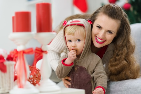 smiling young mother and eat smeared baby eating Christmas cookie photo