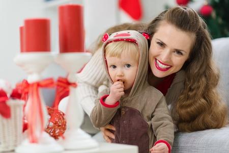 smeared baby: sonriente joven madre y su beb� comer untado comer galletas de Navidad