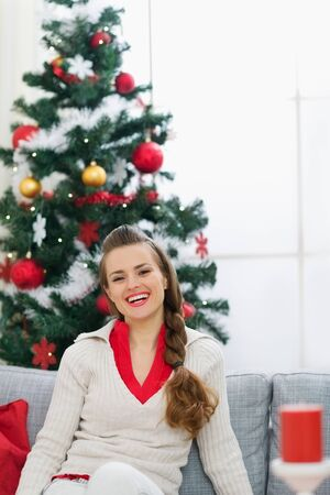 Portrait of smiling young woman near Christmas tree Stock Photo - 15015222