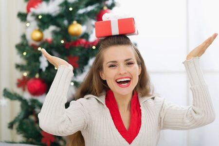 Smiling young woman balancing Christmas present box on head Stock Photo - 15015212