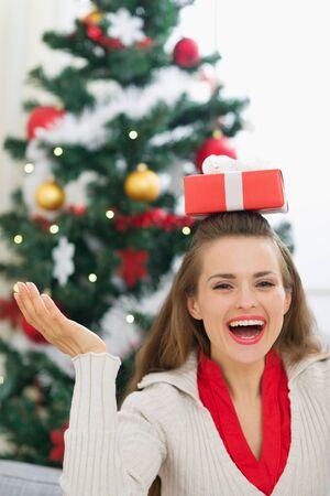 Happy young woman balancing Christmas present box on head Stock Photo - 15015204