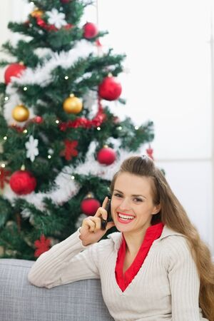 Happy young woman speaking mobile phone near Christmas tree photo