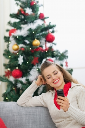 Happy young woman writing sms near Christmas tree Stock Photo - 15015047