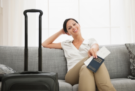Smiling young woman with bag holding passport and air ticket Stock Photo - 15015288