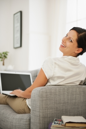 Smiling young woman sitting on couch and working on laptop
