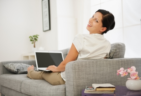 Smiling young woman sitting on couch and working on laptop Stock Photo - 15015269
