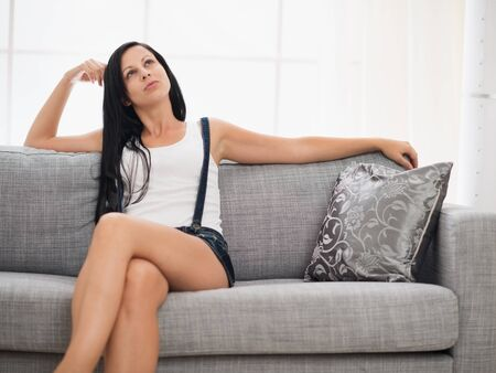 sagacious: Thoughtful young woman sitting on couch in living room Stock Photo