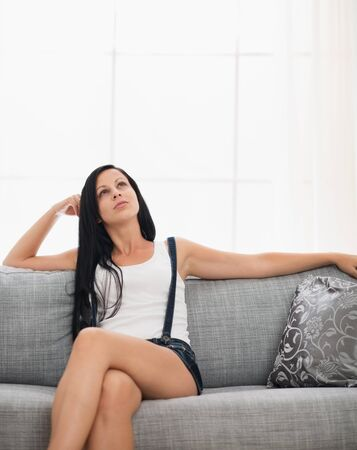 sagacious: Thoughtful girl sitting on couch in living room Stock Photo