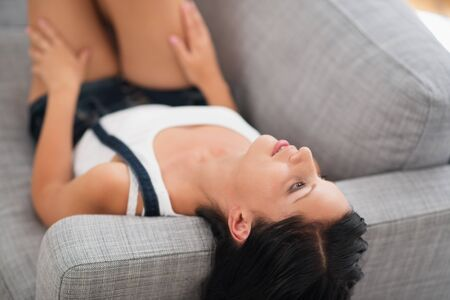 Thoughtful young woman laying on couch Stock Photo - 15015329