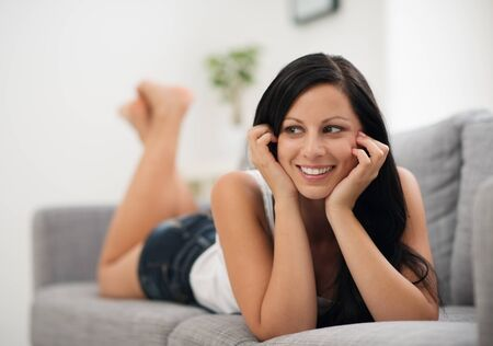 Portrait of happy young woman laying on sofa and looking on copy space Stock Photo - 15007378