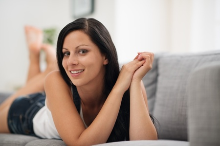 Portrait of happy young woman laying on sofa Stock Photo - 15015293