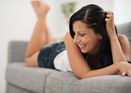 Portrait of laughing young woman laying on couch Stock Photo - 15015287