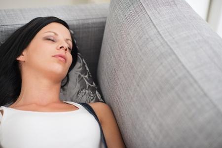 divan: Junge Frau schlafend auf Couch Lizenzfreie Bilder