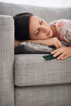 Young woman sleeping with pack of tablets photo