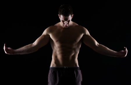 Strong muscular man posing on black photo