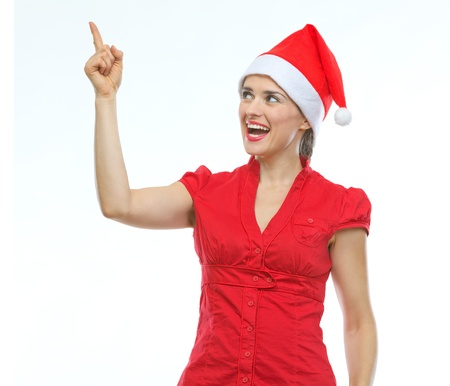 Happy young woman in Christmas hat pointing up Stock Photo - 15366681