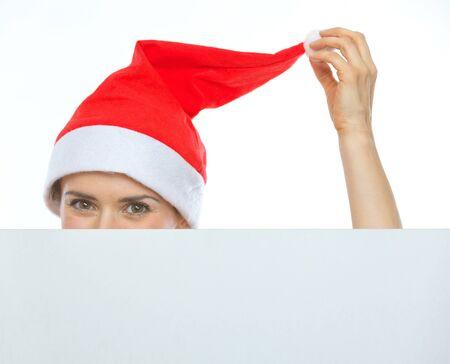 Closeup on female head in Christmas hat hiding behind blank billboard Stock Photo - 15366703
