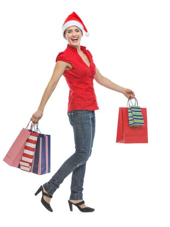 Happy young woman in Christmas hat with shopping bags walking Stock Photo - 15366683