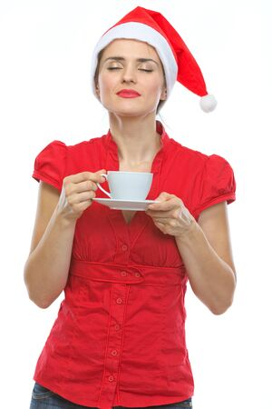 Young woman in Christmas hat enjoying cup of coffee photo