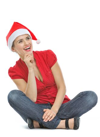 Happy young woman with Christmas hat sitting on floor and looking on copy space Stock Photo - 15366692