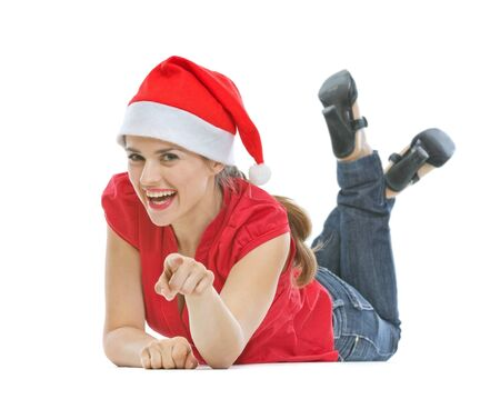 Happy young woman with Christmas hat laying on floor and pointing in camera Stock Photo - 15366651