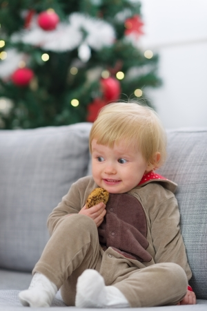 Scared baby in Christmas deer suit with cookie Stock Photo - 15350602