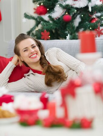 Happy young woman laying on couch near Christmas tree Stock Photo - 15350595