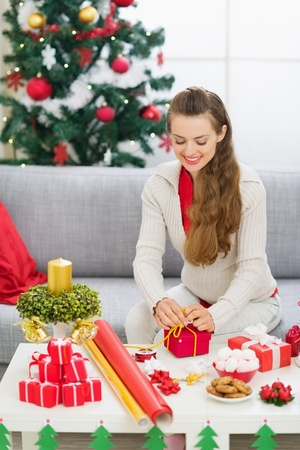 Happy young woman preparing Christmas gift Stock Photo - 15366347