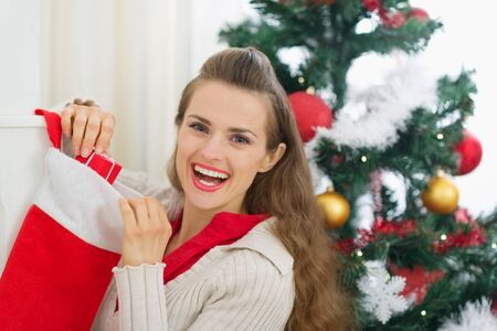 Smiling young woman checking Christmas socks Stock Photo - 15366317