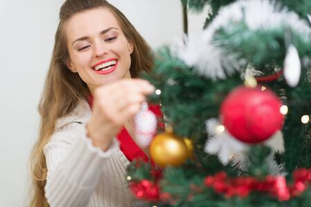 Smiling young woman decorating Christmas tree Stock Photo - 15366329