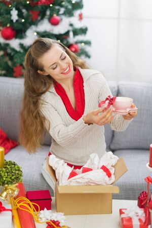 Happy young woman packing Christmas present parcel Stock Photo - 15366316