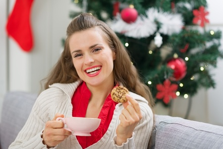Happy young woman near Christmas tree with cup and cookie Stock Photo - 15366318