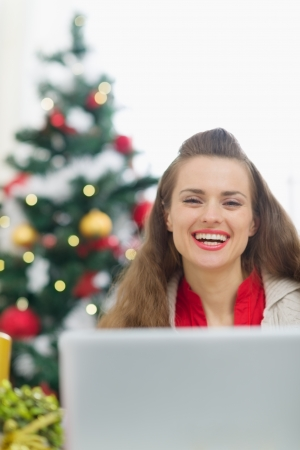 Happy young woman near Christmas tree with laptop Stock Photo - 15366323