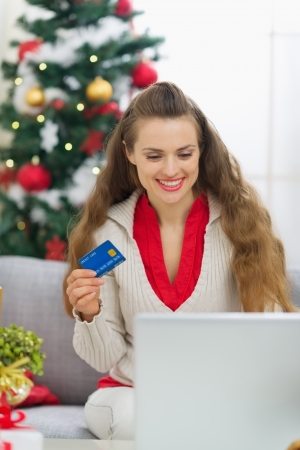 Happy young woman near Christmas tree making online purchases Stock Photo - 15366350