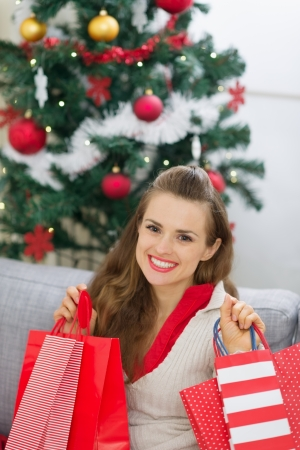 Happy young woman near Christmas tree with shopping bags photo