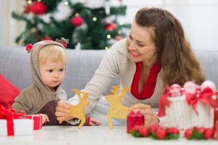 Mother showing baby Christmas deer shaped cookies Stock Photo - 15366353