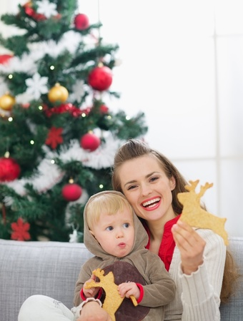 christmas baby: Mother and baby eating Christmas deer shaped cookies Stock Photo